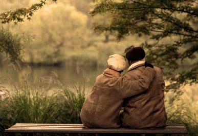 altes-ehepaar-sitzt-zusammen-auf-parkbank-und
